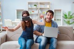 La familia joven que juega a juegos con los vidrios de la realidad virtual Imagen de archivo libre de regalías