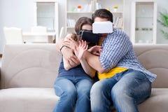 La familia joven que juega a juegos con los vidrios de la realidad virtual Fotos de archivo