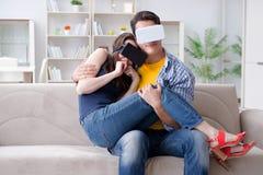 La familia joven que juega a juegos con los vidrios de la realidad virtual Fotografía de archivo libre de regalías