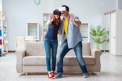 La familia joven que juega a juegos con los vidrios de la realidad virtual Fotografía de archivo