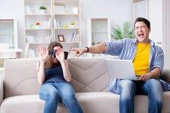 La familia joven que juega a juegos con los vidrios de la realidad virtual Foto de archivo libre de regalías