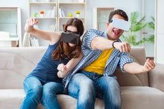 La familia joven que juega a juegos con los vidrios de la realidad virtual Imagenes de archivo