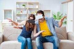 La familia joven que juega a juegos con los vidrios de la realidad virtual Fotos de archivo libres de regalías