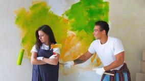La familia joven repara en nuevo plano Pares - pared de la pintura en el apartamento Hombre y mujer que hacen la revisi?n de la c almacen de metraje de vídeo