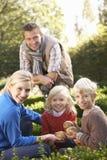 La familia joven se sienta junta en jardín Imagen de archivo libre de regalías