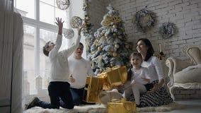 La familia joven se vistió en la ropa blanca, se sienta en el piso cerca del árbol de navidad en la sala de estar con una ventana metrajes