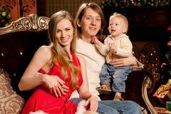 La familia joven sonriente feliz cerca del árbol de navidad celebra nuevo Fotografía de archivo