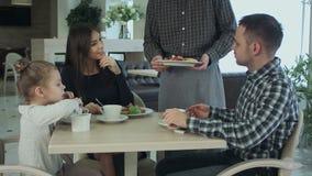 La familia joven toma una comida en café o restaurante El camarero incurre en una equivocación y confunde platos Mirada del padre almacen de video
