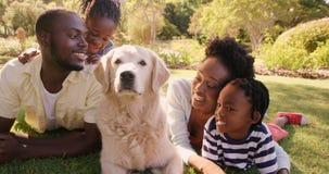 La familia linda está mintiendo en la hierba con un perro metrajes