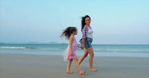 La familia, la madre y la hija jovenes están caminando a lo largo de la familia feliz de la costa que camina en costa de mar almacen de video