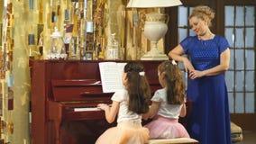 La familia, la madre y las hijas aprenden jugar el piano juntas en hogar almacen de video