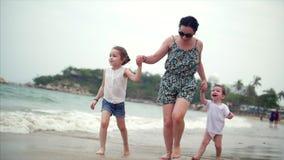 La familia, la madre y los niños jovenes están caminando a lo largo de la familia feliz de la costa que camina en costa de mar metrajes