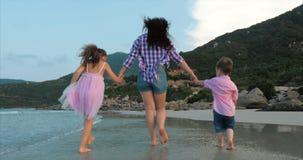 La familia, la madre y los ni?os jovenes est?n caminando a lo largo de la familia feliz de la costa que camina en costa de mar almacen de metraje de vídeo