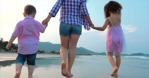 La familia, la madre y los ni?os jovenes est?n caminando a lo largo de la familia feliz de la costa que camina en costa de mar metrajes