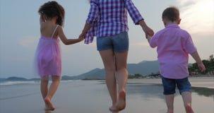 La familia, la madre y los ni?os jovenes est?n caminando a lo largo de la familia feliz de la costa que camina en costa de mar almacen de video