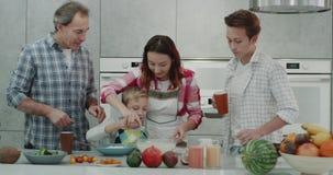 La familia madura tiene un rato agradable junta que prepara la comida junta en una cocina moderna, tiempo de desayuno 4K metrajes