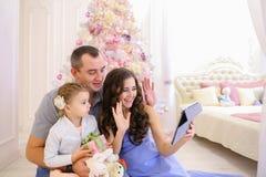 La familia moderna habla con los parientes en Skype en dormitorio espacioso Fotografía de archivo