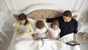 La familia moderna utiliza los dispositivos móviles Dos niños y sus padres están pasando el fin de semana juntos que miente en la almacen de metraje de vídeo