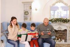 La familia moderna y móvil, dos hijos y el marido y la esposa están ocupados Imágenes de archivo libres de regalías
