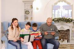 La familia moderna y móvil, dos hijos y el marido y la esposa están ocupados Fotografía de archivo libre de regalías
