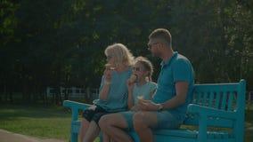 La familia multi de la generación que come helado en banco metrajes
