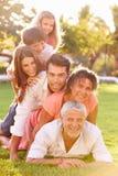 La familia multi de la generación que miente adentro llena para arriba en hierba junta Imagen de archivo