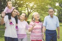 La familia multi feliz de la generaci?n se coloca en el parque fotos de archivo