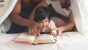 La familia multirracial en dormitorio debajo de la manta lee una enciclopedia de los niños metrajes