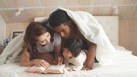 La familia multirracial en dormitorio debajo de la manta lee una enciclopedia de los niños almacen de metraje de vídeo