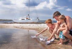La familia (padre e hijos) está en la playa. Fotografía de archivo