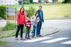 La familia pasando el paso de peatones Fotos de archivo