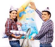 La familia pega el papel pintado en casa. Foto de archivo