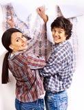 La familia pega el papel pintado en casa. Fotos de archivo