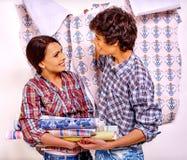 La familia pega el papel pintado en casa Imágenes de archivo libres de regalías