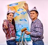 La familia pega el papel pintado en casa Fotografía de archivo