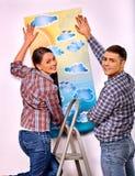 La familia pega el papel pintado en casa Imagen de archivo