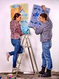 La familia pega el papel pintado en casa Fotos de archivo libres de regalías