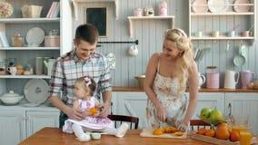 La familia que come el desayuno sano en cocina, la madre feliz de la mamá de la familia y el papá engendran con mañana del niño d almacen de metraje de vídeo
