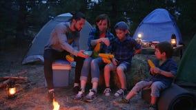 La familia que come el maíz de hacia fuera enciende, viaje acampando, comida campestre en el bosque, mamá, papá y los hijos comen almacen de metraje de vídeo