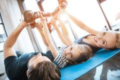 La familia que ejercita con las pesas de gimnasia en el estudio de la aptitud, pesas de gimnasia en corazón forma Foto de archivo libre de regalías