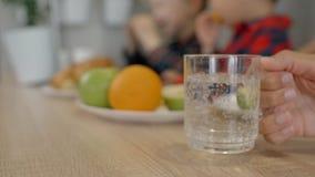 La familia que se sienta en la tabla en cocina, mujer está tomando el vidrio de agua metrajes