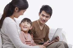La familia que se sienta junta en el sofá usando el ordenador portátil, madre está mirando a su hija sonriente, tiro del estudio Fotografía de archivo libre de regalías