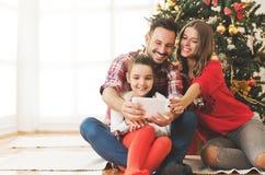 La familia recolectó alrededor de un árbol de navidad, usando una tableta imagenes de archivo