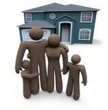 La familia se coloca delante de casa Imagen de archivo libre de regalías