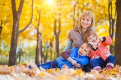 La familia se divierte en el parque del otoño foto de archivo