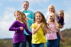 La familia se está ejecutando al aire libre Imagenes de archivo