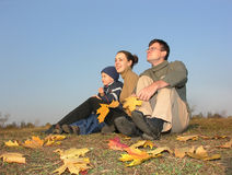 La familia se sienta con las hojas de otoño Fotos de archivo libres de regalías