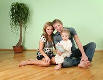 La familia se sienta en el cuarto en el suelo 2 Imagen de archivo