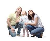 La familia se sienta, las manos del asimiento y mirada para arriba imagen de archivo libre de regalías