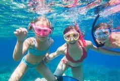 La familia se zambulle en el mar en máscaras Imágenes de archivo libres de regalías